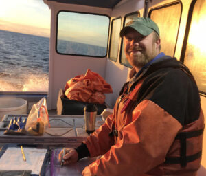 man records data on boat