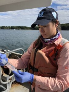 Woman looks at water sample on boat