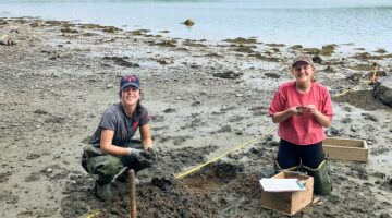Two students working in the intertidal zone of the Damariscotta River, looking at camera while counting shellfish and crabs.